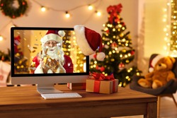 Computer on table in cozy room with hanging red hat and with Santa Claus on screen blowing golden confetti, sending love, wishing Merry Christmas and Happy New Year online and making miracle come true