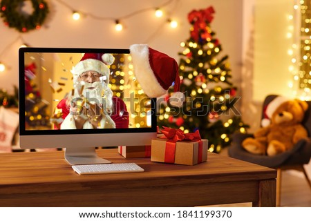 Photo of  Computer on table in cozy room with hanging red hat and with Santa Claus on screen blowing golden confetti, sending love, wishing Merry Christmas and Happy New Year online and making miracle come true