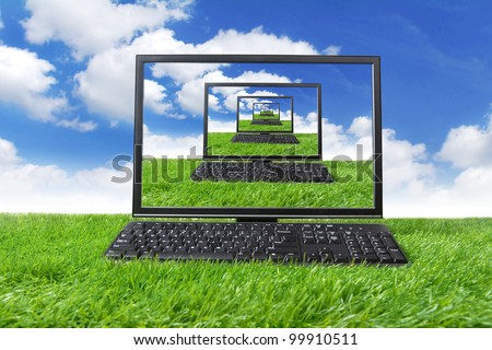 Computer on the green grass. Shot on meadow