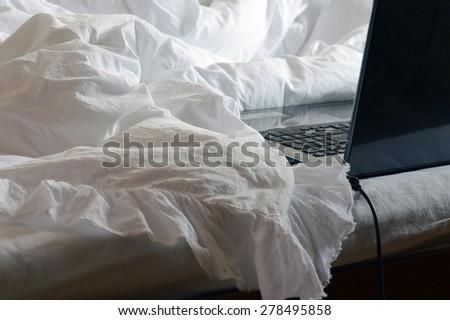 computer on white blanket, white interior, white sheet,bedroom