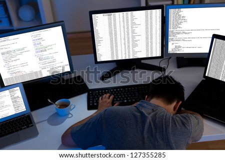 Computer programmer sleeping in the office at night