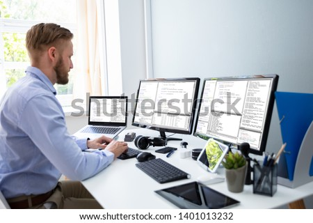 Photo of Computer programmer writing program code on computer in office