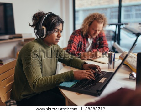 Computer programmers wearing headphones coding on laptop with colleagues working around at startup office. Young professionals working at a tech startup office.