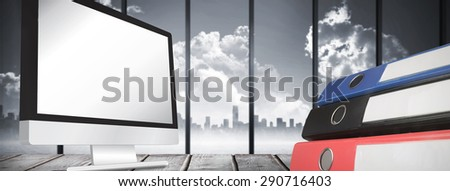 Computer screen against room with large window looking on city skyline