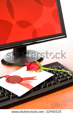 Computer screen and Valentine card with rose on keyboard