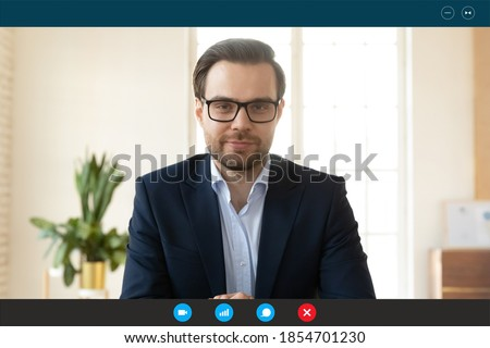 Computer screen close up view handsome happy 30s confident businessman in formal wear and eyeglasses holding web camera negotiations video call with colleagues partners, distant communication concept.