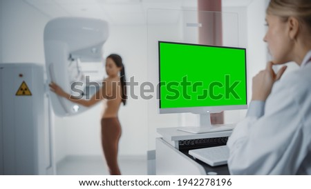 Computer Screen in Hospital Radiology Room: Beautiful Multiethnic Adult Woman Standing Topless Undergoing Mammography Screening Procedure. Screen Showing Green Mock-up Chroma Key Template. Foto stock ©