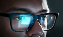 Computer screen light reflect from glasses. Close up of eyes. Business man, coder or programmer working late at night with laptop. Thoughtful focused guy in dark. Reflection of monitor.