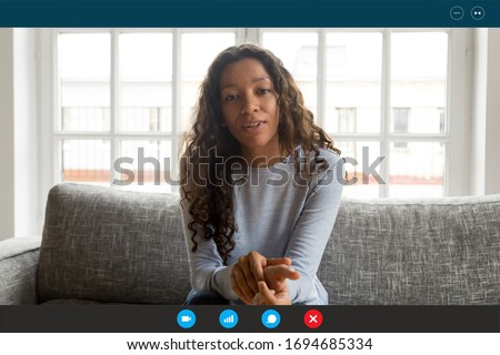 Computer screen view african woman sit on couch looking at webcam, share news with friend, applicant pass job interview by videoconference app, communicates with employer from home, video call concept