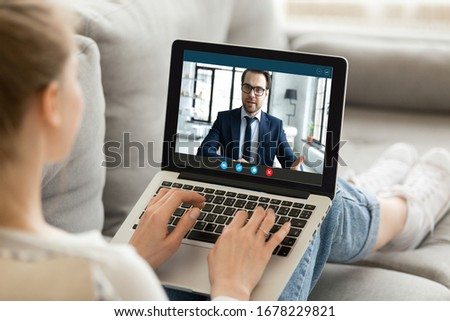 Computer screen view over woman shoulder, girl sit on sofa got information from manager distantly, work from home due corona virus, make videocall communicates use video conference application concept