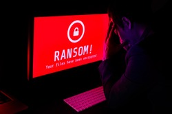 Computer screen with ransomware attack file encrypted alerts in red, a man get stress with keyboard in a dark room, ideal for online security failure and digital crime, long exposure selective focus