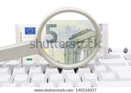 Computer security concept with keyboard, magnifying glass and money