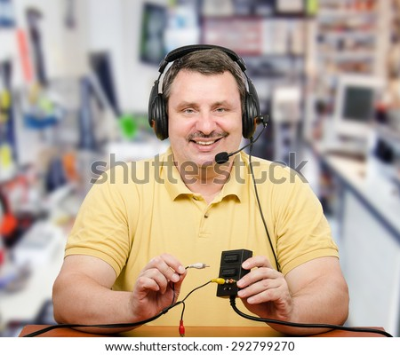 Computer service technician is consulting via internet. He explains how to use audio-video adapter