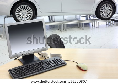 Computer stands on wooden desk and new car stands in office of car shop.