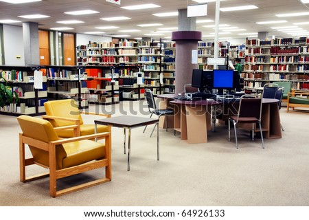 Computer station at the university college library with seating area in the foreground. One young female student searching far in the background.