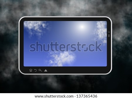 Computer tablet with blue sky on the screen and stormy clouds in the background / Tablet and clouds