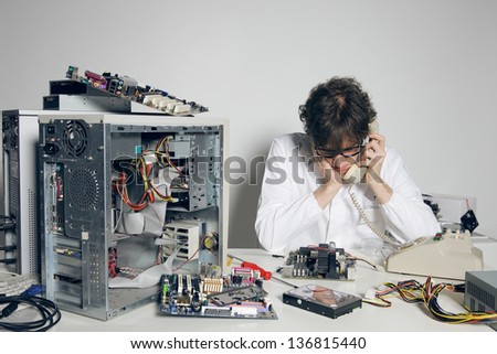 Computer technician in his laboratory is talking on the phone