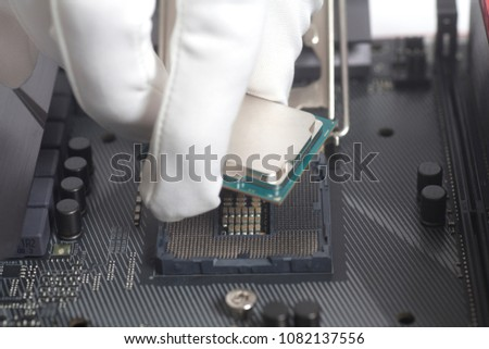 Stock Photo Computer technician installing CPU into motherboard.