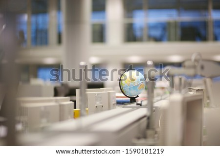 Computer terminals and globe in office