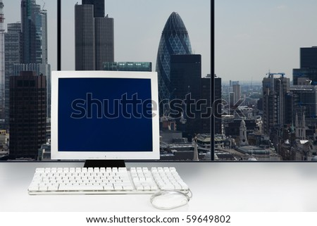 Computer with blank blue screen monitor for copy space and the city of London in the background