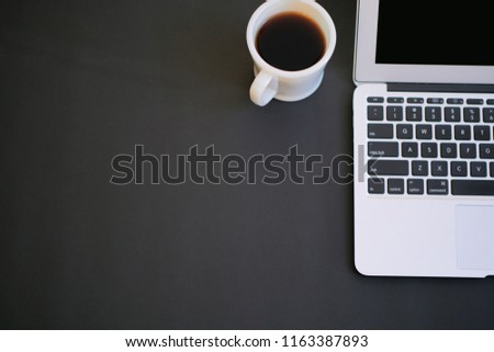 Computer with cup of coffee on the black background