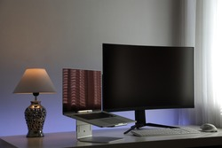 Computer workstation ideal for the home office consisting of a gray laptop on a stand, a large curved and black monitor, a white lamp, a white keyboard and a white optical mouse with backlighting