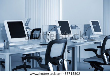 Computers with LCD screens in modern office in the blue tilt