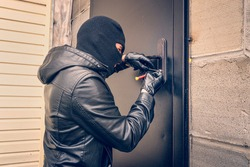 Con Man Picking Lock with Black Leather Gloves with the help of special lock picks at Night