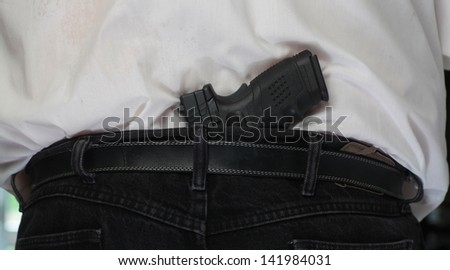 Concealed Weapon/Close view of black automatic pistol tucked into man's belt from behind