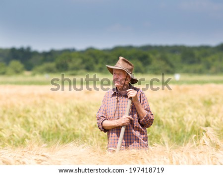 Conceived old man farmer resting in barley field after hard work