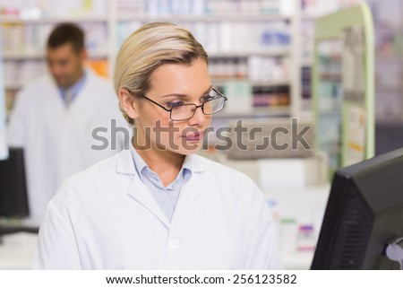 Concentrate pharmacist looking at computer at the hospital pharmacy