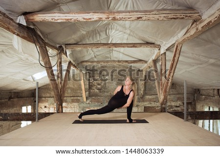 Concentrated. A young athletic woman exercises yoga on an abandoned construction building. Mental and physical health balance. Concept of healthy lifestyle, sport, activity, weight loss, concentration