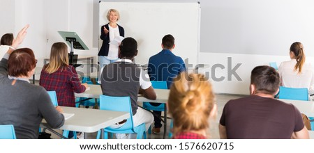 Concentrated adult students of different nationalities with teacher studying in classroom