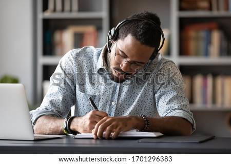 Concentrated African American male student in glasses and wireless headset studying handwriting in notebook, focused biracial man worker in headphones make notes watching webinar or training on laptop