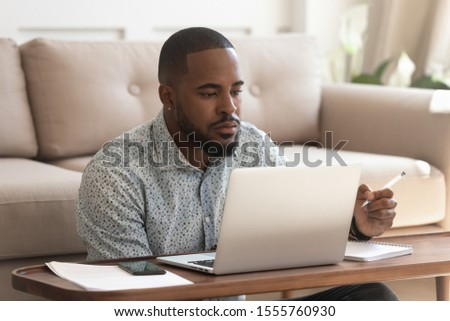 Concentrated african American male student look at laptop screen studying at home make notes in notebook, focused biracial man watch online learning course or webinar on computer writing or outlining
