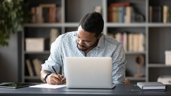 Concentrated African American male worker sit at desk handwrite watching webinar or training on laptop, focused biracial man make notes busy studying working on computer at workplace in office