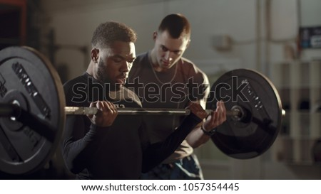 Concentrated African-American sportsman training bicep with heavy barbell under control of professional coach in gym.