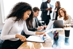 Concentrated african american woman doing paperwork, sitting in modern office on conference. Focused business lady learning financial graphs, working on corporate project at briefing meeting