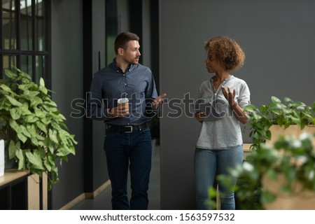 Concentrated african american young trainee asking questions to confident caucasian male team leader, walking together during work pause at coworking office. Couch consulting female intern employee.