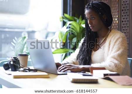 Concentrated afro american  freelancer with cornrows typing on keyboard of modern laptop text information in internet websites for searching ideas and creating startup project of business company - Shutterstock ID 618144557