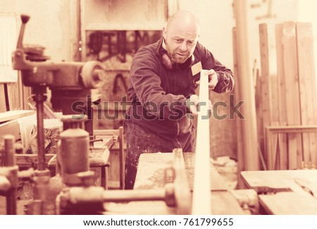 Concentrated artisan in a blue robe is shaping timber on a woodworking machine at the factory - Shutterstock ID 761799655