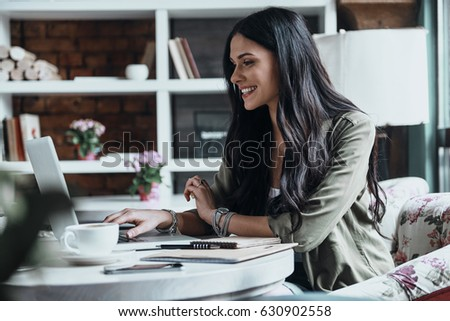 Concentrated at work. Beautiful young woman using laptop and looking at it while sitting at her working place