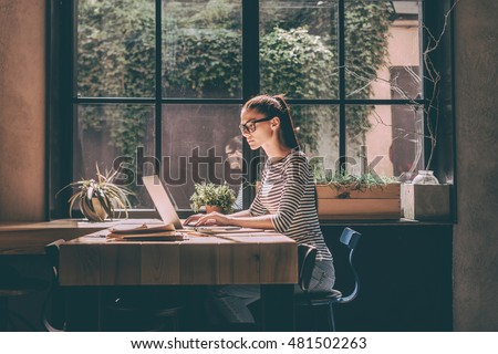 Concentrated at work. Confident young woman in smart casual wear working on laptop while sitting near window in creative office or cafe