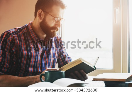 concentrated bearded man reading book #334592630
