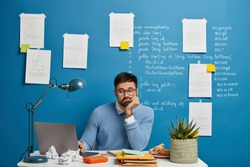 Concentrated bearded web developer improves new website version, sits at white table, loaded with notepads, snack, cup of tea and potted plant, looks sadly at problem of project, leans at hand