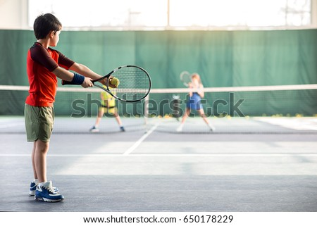 Concentrated boy pitching tennis ball
