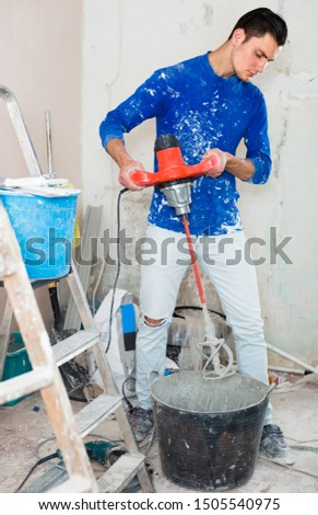 concentrated builder mixing plaster in bucket using electric mixer in repairable room #1505540975