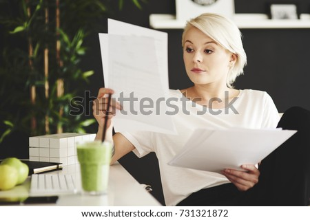 Concentrated businesswoman comparing documents at office  #731321872