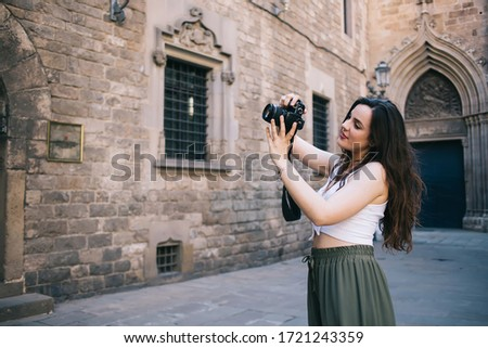 Photo of Concentrated caucasian woman photographer focusing while making picture on digital equipment on street, young 20s female tourist taking picture on architecture building on camera during trip