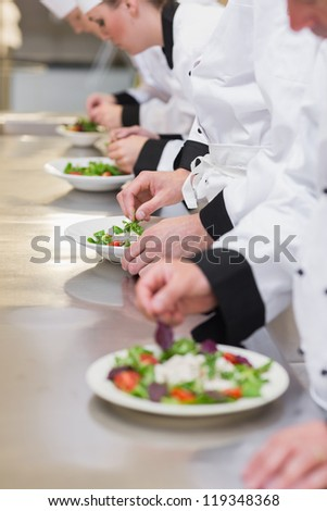 Concentrated Chef's team garnishing salads in the kitchen